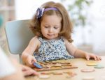 Small toddler or baby kid playing with puzzle shapes on low table in children room, kindergarten or preschool.